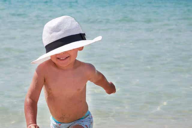 Barn med hatt springer vid vattnet.