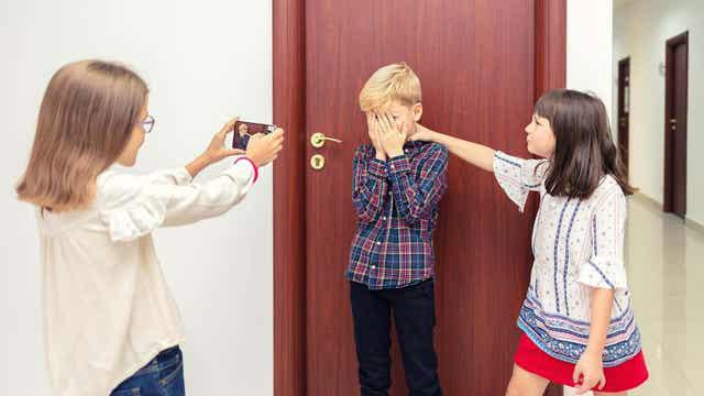 Två tjejer tar kort av en pojke som inte vill vara med på bild.