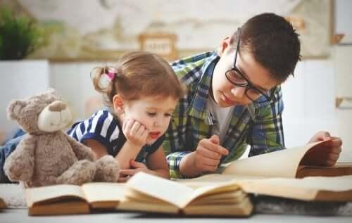 Bror hjälper sin syster med läxor.