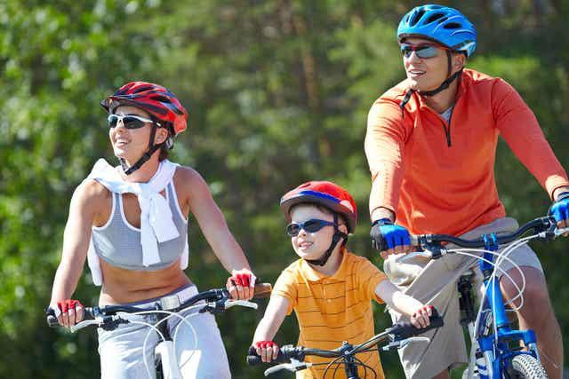 Familj är ute och cyklar tillsammans.
