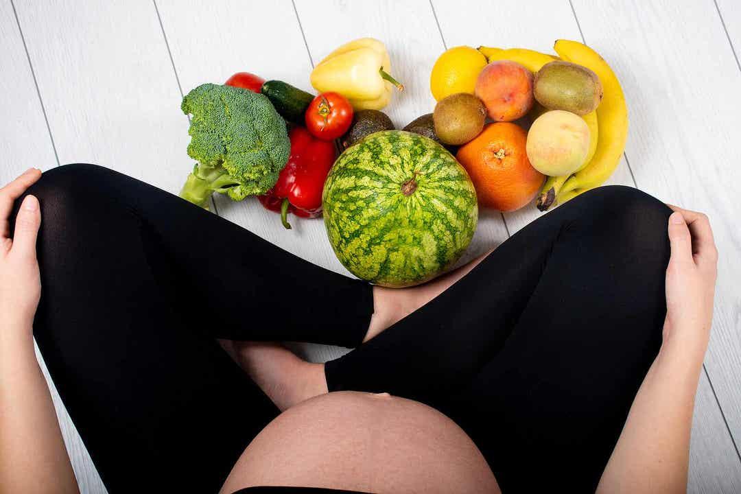 vitamin K under graviditeten: gravid kvinna sitter vid frukt och grönt