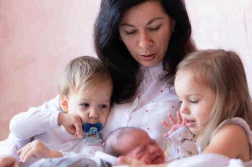 hälsa på en nyfödd: mamma med nyfödd baby och två äldre syskon