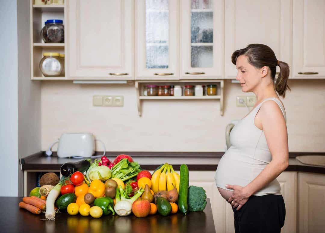 gravid kvinna i kök framför massor av grönsaker