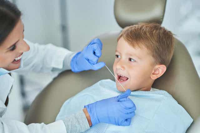 Tandläkare rengör barns tänder med tandtråd.