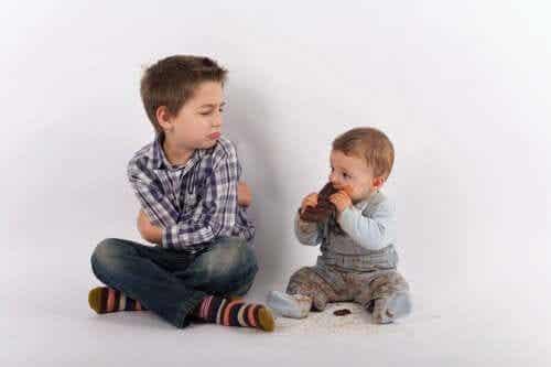Avundsjuk storebror sitter sur bredvid sin lillebror.