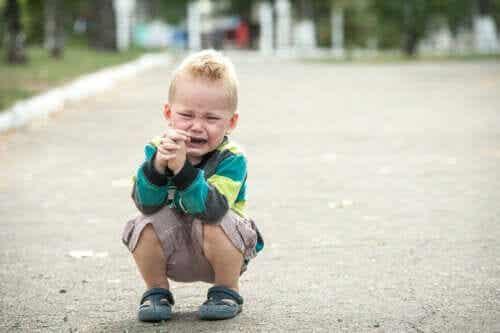Barn sitter på gatan och gråter.
