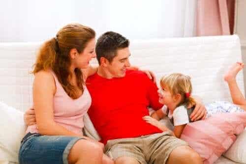 Föräldrar sitter i soffan med sin dotter.