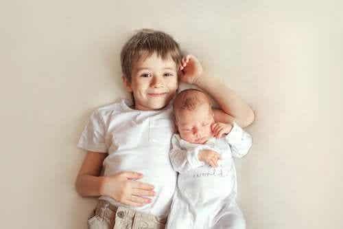 Glad storebror ligger bredvid sitt nya syskon.