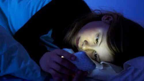 flicka med mobil i säng