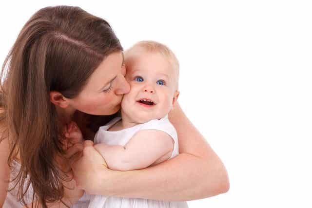Mor pussar på sin bebis kind.
