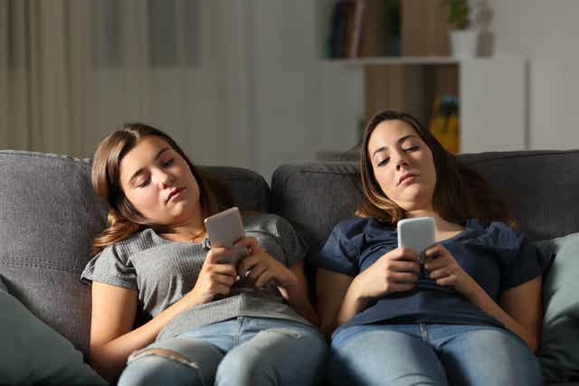 Två ungdomar sitter i soffan med mobilen i handen.