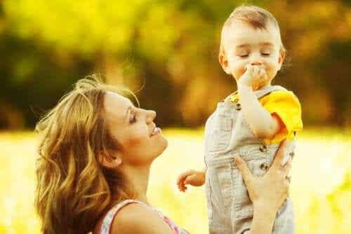 Stimulera språkutvecklingen: En mamma leker med sitt barn på en äng.